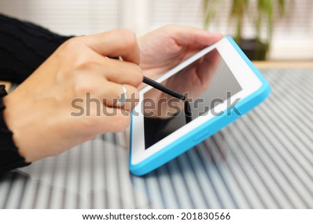 Closeup of woman working with pen on tablet pc - stock photo