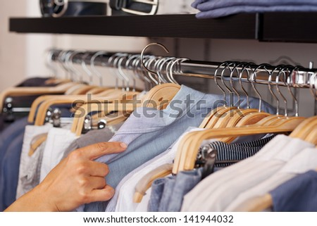 Closeup of womans hand selecting shirt from rack in clothing shop - stock photo