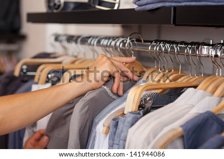 Closeup of womans hand selecting shirt from rack in clothing store - stock photo