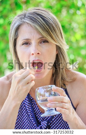 Closeup of women taking medicine in pill with water glass - stock photo