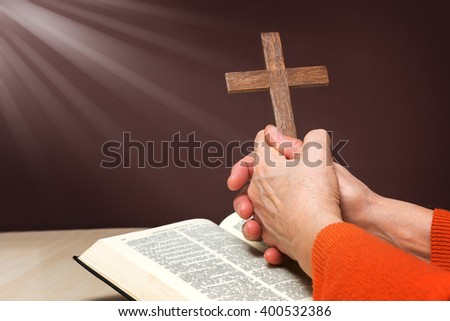 Closeup of wooden Christian cross and hand next on holy Bible