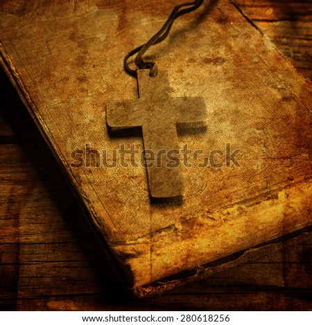Closeup of wooden Christian cross on bible - stock photo