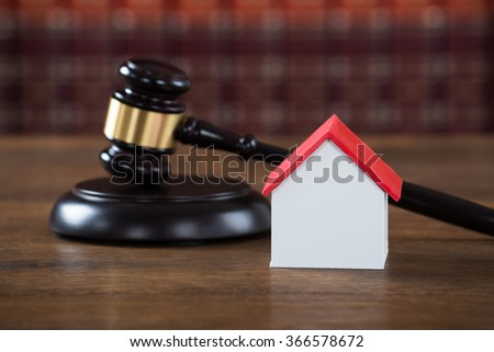 Closeup of wooden mallet with house model on table in courtroom
