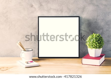 Closeup of wooden surface with blank frame, flowerpot, iron mug with pencils and glasses on concrete background. Mock up - stock photo