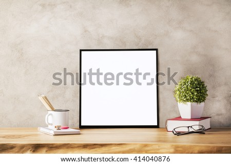 Closeup of wooden table with blank frame, flowerpot, iron mug with pencils and glasses on concrete background. Mock up - stock photo