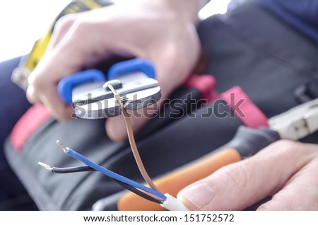 Closeup of worker's hands cutting electric wires with pliers. - stock photo