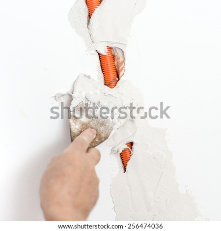 Closeup of workers hand plastering Flexible Corrugated Cable Duct into the wall. - stock photo