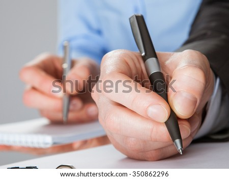 Closeup of working business team taking notes, concept of successful team work - stock photo