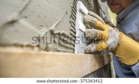 Closeup of workman carefully positioning an ornamental tile in a glue while tiling a wall.