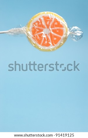 Closeup of wrapped orange lollipop on a stick against blue background with copy space