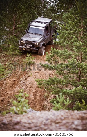 Closeup of 4x4 truck driving downhill  on the edge of hill - stock photo