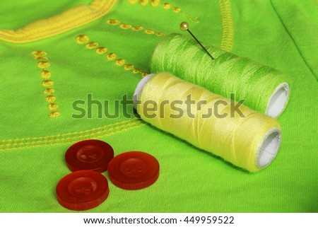 Closeup of yellow and green thread and orange buttons on light green background. Sewing accessories. - stock photo