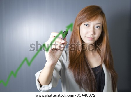 Closeup of young Asian business woman drawing graph on transparent glass or foil.