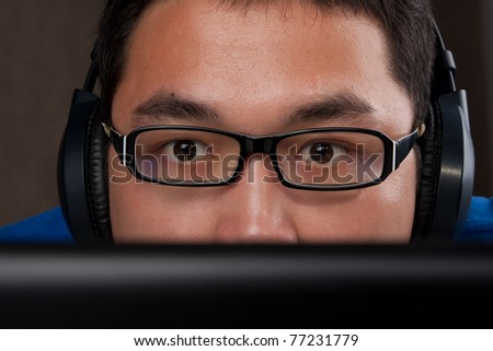 closeup of young asian man playing games on laptop computer on gray background