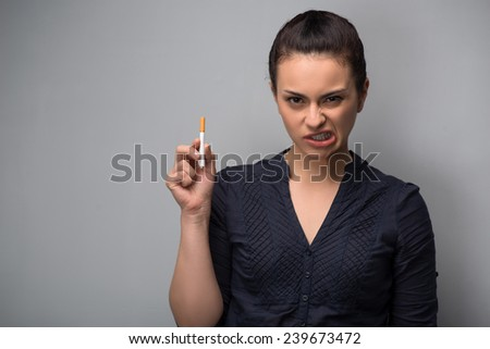 Closeup of young attractive Caucasian woman determined girl holding cigarette and twisting her mouth in disgust. Quit smoking. Studio shot isolated on grey. Addiction concept - stock photo