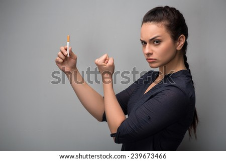 Closeup of young attractive Caucasian woman determined girl holding cigarette showing fist. Quit smoking. Studio side view shot isolated on grey. Addiction concept - stock photo