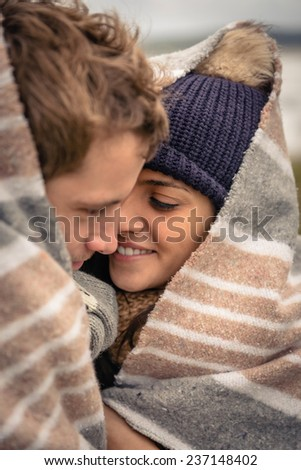 Closeup of young beautiful couple embracing outdoors under striped blanket in a cold day - stock photo