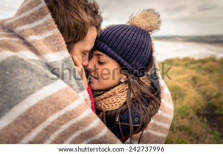 Closeup of young beautiful couple embracing under blanket in a cold day with sea and dark cloudy sky on the background - stock photo