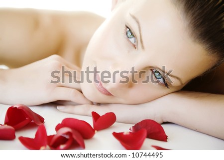 closeup of young beautiful female face, lying on a bed, maybe enjoying a beauty-treatment. - stock photo