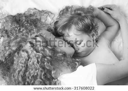 Closeup of young beautiful loving mother with soft curly hair kissing small tiny cute male lovely baby sleeping indoor in bed with white linen black and white, horizontal picture - stock photo