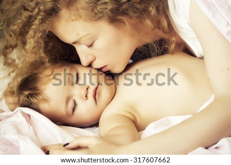Closeup of young beautiful loving woman with light blonde curly hair sleeping with little tiny cute male lovely baby indoor in bed with white linen lying close to each other, horizontal picture - stock photo