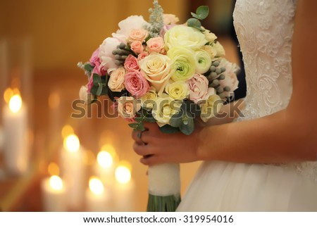 Closeup of young bride in white dress holding one beautiful fresh wedding bouquet of rose flowers pastel colors with blazing candles on blur warm light background, horizontal picture  - stock photo
