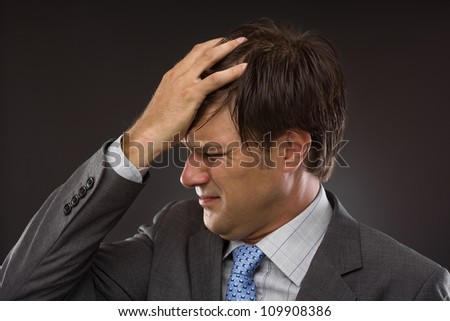 Closeup of young business man with headache on gray - stock photo