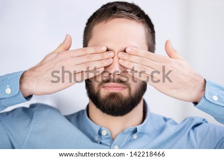 Closeup of young businessman covering his eyes with hands in office