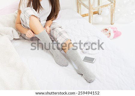 Closeup of young Caucasian brunette woman sitting in bed with socks and pajamas at home in the morning. Teenage girl with smartphone and headphones dressing. No retouch, horizontal. - stock photo