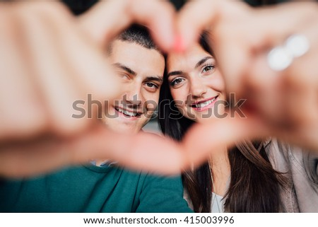Closeup of young couple making heart shape with hands - stock photo
