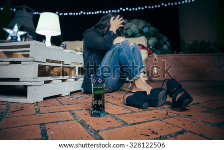 Closeup of young drunk woman holding her head sitting in the floor after outdoors party. Fun and alcohol and drugs problems concept. - stock photo