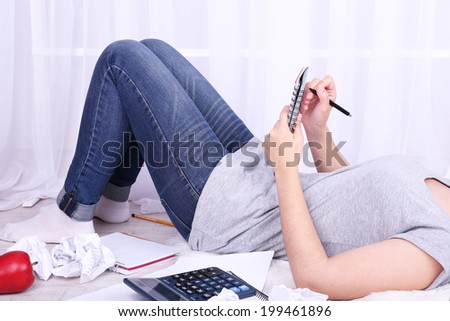 Closeup of young female student lying on floor and studying, on light background