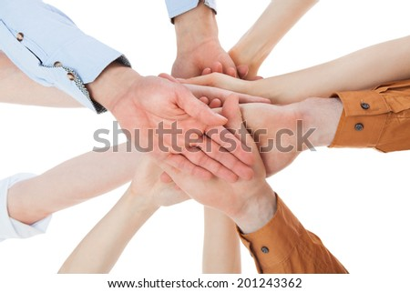 Closeup of young friends with their hands stacked together on white background