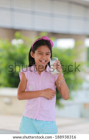 Closeup of young girl drinking milk. - stock photo