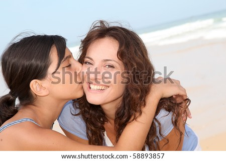 Closeup of young girl kissing her mom at the beach