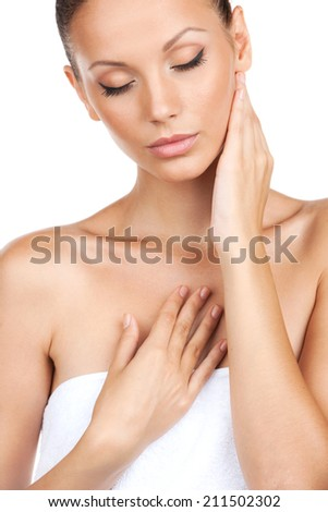 Closeup of young girl with fresh healthy skin. Beautiful young woman touching her skin with eyes closed - stock photo