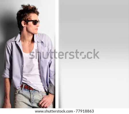 Closeup of young, handsome man thinking. Standing against wall - stock photo