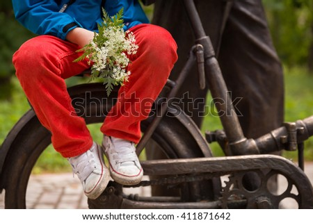 Closeup of young kid boy with wild flowers sitting on metal bicycle, on natural background outdoors, horizontal picture. - stock photo