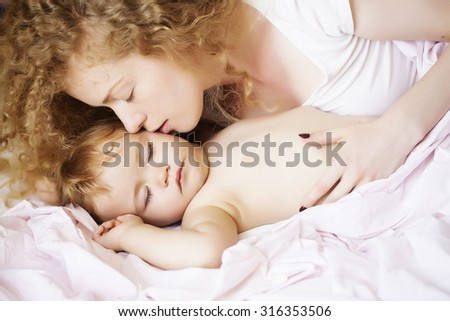 Closeup of young loving woman with light blonde curly hair sleeping with little tiny cute male lovely baby indoor in bed with white linen lying close to each other, horizontal picture - stock photo
