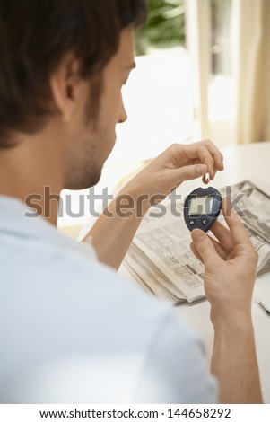 Closeup of young man measuring sugar with blood glucose meter at home - stock photo