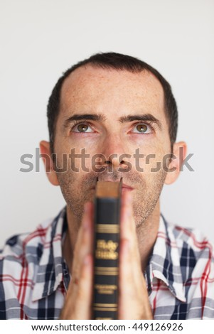 Closeup of Young Man Praying. Mans hands clasped in prayer with Holy Bible - stock photo