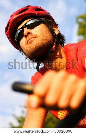 Closeup of young man riding a mountain bike in the forest on a sunny day - stock photo