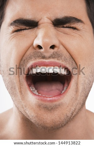Closeup of young man screaming with eyes closed on white background - stock photo