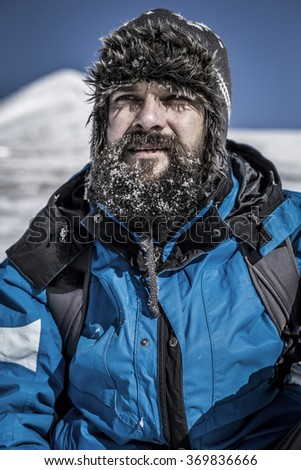 Closeup of  young man with snowy beard in the mountains - stock photo