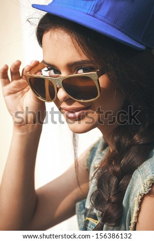 Closeup of Young sexy girl in blue cap and jeans jacket  looking through golden sunglasses .  Outdoors, lifestyle. - stock photo