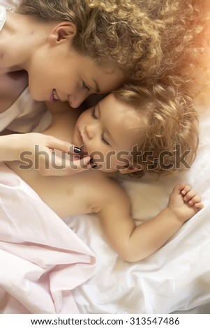 Closeup of young smiling loving mother with light blonde curly hair touching small tiny cute male lovely baby sleeping indoor in bed with white linen lying close to each other, vertical picture
