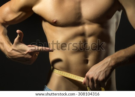 Closeup of young stripped guy with sexual strong muscular beautiful tan body showing finger on yellow tape measure round waist standing on black background, horizontal picture - stock photo