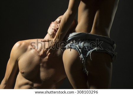 Closeup of young stripped pair of sexy woman in jeans with beautiful buttocks and man with strong muscular body standing on black studio background, horizontal picture - stock photo