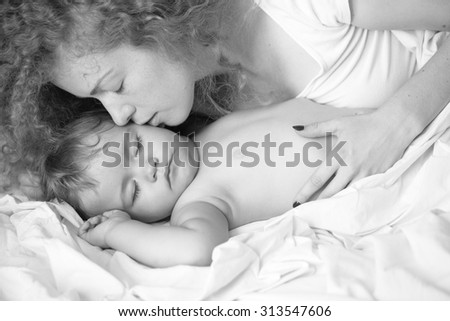 Closeup of young tender loving mother with soft curly hair embracing and kissing small tiny cute male lovely baby sleeping indoor in bed with white linen black and white, horizontal picture - stock photo
