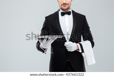 Closeup of young waiter in tuxedo holding metal empty tray and napkin - stock photo